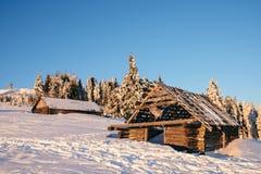 Casa di legno abbandonata nelle montagne di inverno ad alba Fotografia Stock