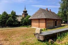 Casa di legno accanto alla chiesa regionale antica in villaggio polacco storico, regione di Lesser Poland, Polonia Fotografia Stock