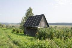 Casa di legno accanto alla strada del villaggio circondata da pianta Fotografie Stock