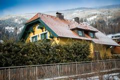 Casa di legno in alpi contro le alte montagne Immagini Stock