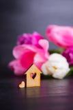 Casa di legno con il foro nella forma di cuore con i tulipani rosa Fotografia Stock