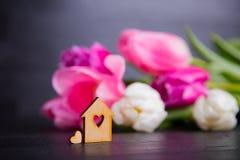 Casa di legno con il foro nella forma di cuore con i tulipani rosa Fotografie Stock Libere da Diritti