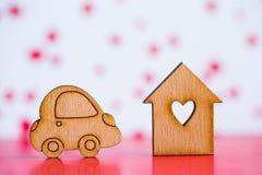 Casa di legno con il foro nella forma di cuore con l'icona di legno dell'automobile sopra Fotografie Stock