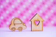 Casa di legno con il foro nella forma di cuore con l'icona di legno dell'automobile sopra Fotografia Stock