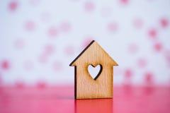 Casa di legno con il foro nella forma di cuore su backgr rosa e bianco Immagine Stock Libera da Diritti