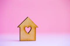 Casa di legno con il foro nella forma di cuore su fondo rosa Fotografie Stock Libere da Diritti