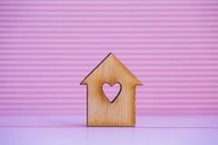 Casa di legno con il foro nella forma di cuore sul backgrou a strisce rosa Fotografia Stock Libera da Diritti