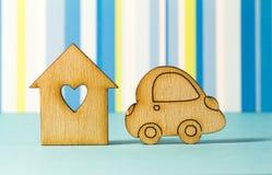 Casa di legno con il foro sotto forma di cuore con l'icona dell'automobile su blu Immagine Stock Libera da Diritti