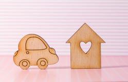 Casa di legno con il foro sotto forma di cuore con l'icona dell'automobile sul perno Fotografia Stock