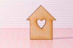 Casa di legno con il foro sotto forma di cuore sul rosa barrato indietro Fotografia Stock