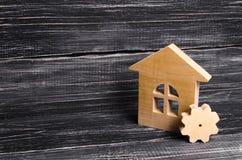 Casa di legno con un ingranaggio su un fondo di legno scuro Il concetto dell'impresa per produzione, manifattura riparazione fotografie stock