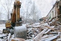 Casa di legno del ceppo di demolizione dell'escavatore in precipitazioni nevose Fotografia Stock Libera da Diritti