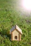Casa di legno del giocattolo sull'erba luminosa Esponga al sole l'abbagliamento dalla destra Copi lo spazio Concetto 6 del bene i fotografia stock libera da diritti