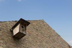 Casa di legno dell'uccello sulla costruzione del muro di mattoni immagini stock libere da diritti