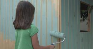 Casa di legno della pittura della ragazza piccola con un rullo archivi video