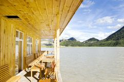 Casa di legno in lago vicino alla montagna Fotografia Stock
