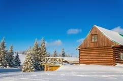 Casa di legno nel paesaggio di inverno, giorno soleggiato Fotografia Stock