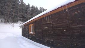 Casa di legno nell'inverno con i ghiaccioli stock footage