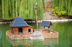 Casa di legno per le anatre in mezzo al lago della città in autunno Fotografie Stock Libere da Diritti