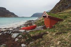 Casa di legno rossa con muschio sul tetto e sulla barca sui precedenti del mare e delle montagne Nella distanza una barca rossa immagini stock libere da diritti