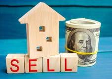 Casa di legno su un fondo blu con la vendita dell'iscrizione vendita della proprietà, casa, bene immobile Alloggiamento acquistab immagine stock