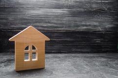 Casa di legno su un fondo concreto grigio Concetto di acquisto e di vendita dell'alloggio, costruzione una casa Affitto degli app fotografia stock libera da diritti