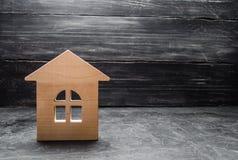 Casa di legno su un fondo scuro Il concetto di acquisto della vendita del bene immobile, affitto di alloggi Servizi di agente imm Fotografie Stock