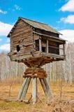 Casa di legno sui pali nel campo immagine stock