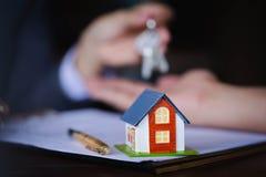 Casa di legno sui precedenti della tavola con il givi dell'agente immobiliare immagini stock libere da diritti