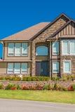 Casa di lusso della famiglia con i fiori freschi sull'iarda anteriore sul fondo del cielo blu immagini stock libere da diritti