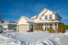 Casa di lusso della famiglia con l'iarda anteriore in neve Immagine Stock