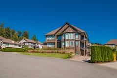 Casa di lusso nel centro della vicinanza con il fondo abbellito del cielo blu e dell'iarda anteriore immagine stock libera da diritti