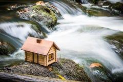Casa di modello accanto ad acqua precipitante Immagine Stock
