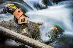 Casa di modello accanto ad acqua precipitante Immagini Stock