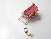 casa di modello di legno con soldi sulla tavola bianca con il rea dello spazio della copia Fotografie Stock