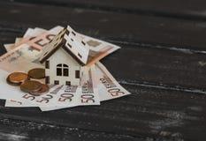 Casa di modello ed euro banconote su fondo di legno scuro Immagine Stock