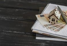 Casa di modello, euro banconote, blocco note su fondo di legno scuro Immagini Stock