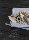 Casa di modello, euro banconote, blocco note su fondo di legno scuro Immagine Stock