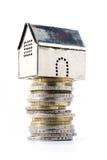 Casa di modello metallica su un mucchio delle monete, isolato su bianco Fotografia Stock