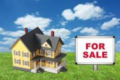 Casa di modello su erba verde con per il segno di vendita Immagine Stock Libera da Diritti