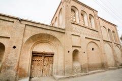 Casa di pietra nella muratura iraniana di stile e porta di legno in una via stretta di vecchia città Fotografia Stock