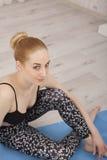 Casa di pratica sulla stuoia blu - esaminare di yoga della bella giovane donna la macchina fotografica Immagine Stock Libera da Diritti
