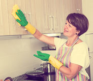 Casa di pulizia della donna del pensionato fotografia stock