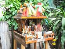 Casa di spirito di Brown in Tailandia con i fiori in un vaso Immagine Stock