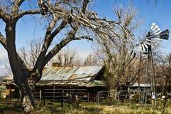 Casa dilapidada de la granja del desierto con el molino de viento Fotos de archivo