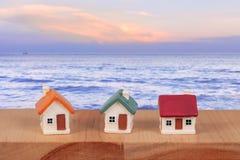 Casa diminuta com scape do mar e para borrar o bokeh claro, casa diminuta da família do amor no suporte de madeira com parede de  imagem de stock
