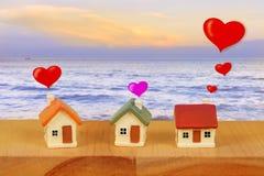 Casa diminuta com scape do mar e para borrar o bokeh claro, casa diminuta da família do amor no suporte de madeira com parede de  fotos de stock