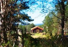 Casa distante dell'azienda agricola della Norvegia nel fondo di legni Fotografie Stock Libere da Diritti