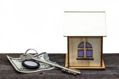 Casa do brinquedo com chaves e dinheiro na placa de madeira velha, no fundo isolado branco imagem de stock