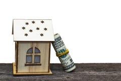 Casa do brinquedo com chaves e dinheiro na placa de madeira velha, no fundo isolado branco fotografia de stock